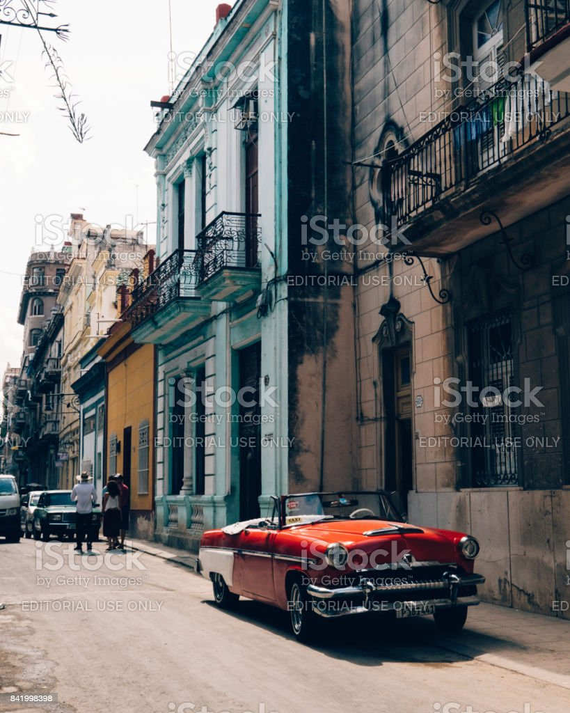 Red classic convertible car parked in front of colorful buildings in Old Havana stock photo