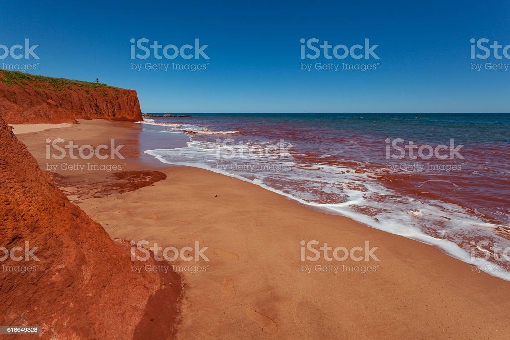 Red Cliffs with contrasting blue sea, with red stained water stock photo