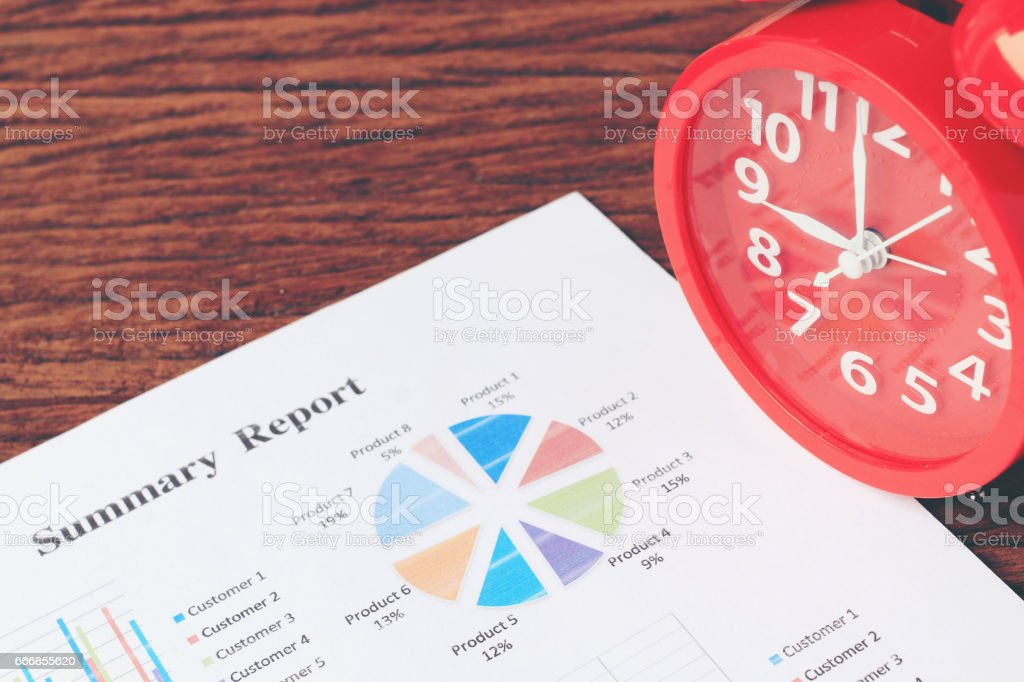 red clock on chart on wooden background. Business background , stock photo