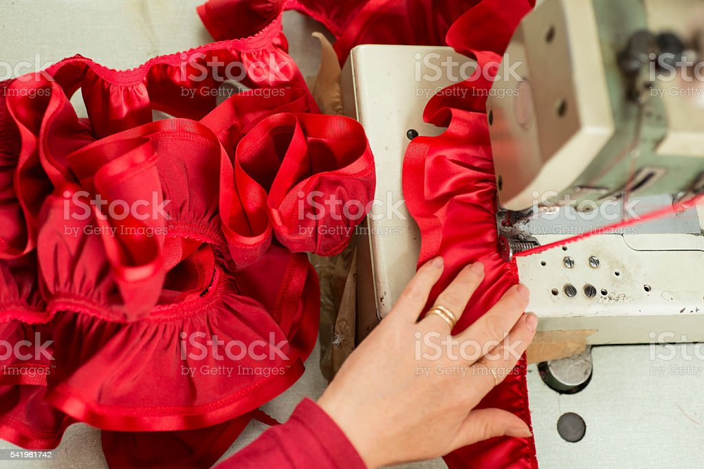 Red Cloth and Ribbon Sewn and Ruffled Through Sewing Machine stock photo