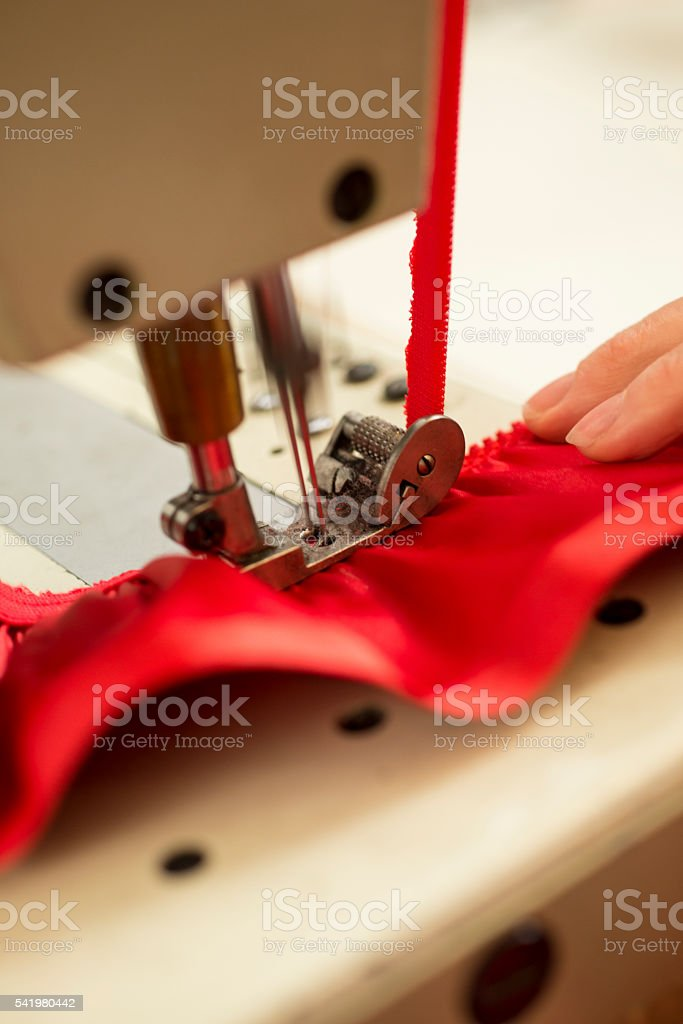 Red Cloth and Ribbon Stitched on Double-Needled Sewing Machine stock photo