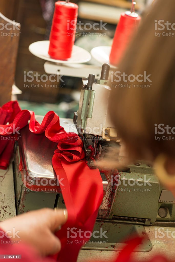 Red Cloth Ruffled in Sewing Machine by Seamstress stock photo