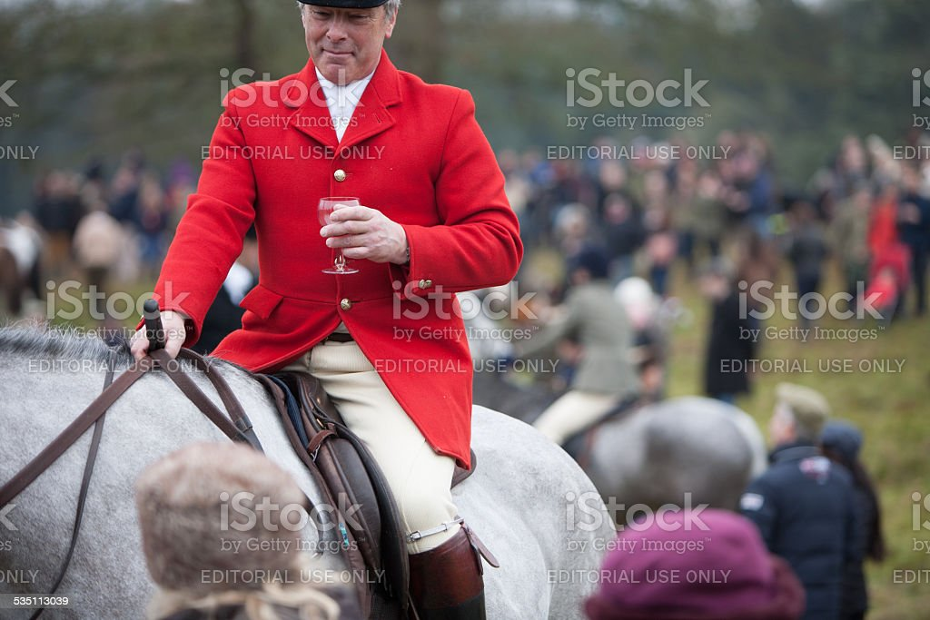 Red Coat Huntsman among a group of hunt supporters stock photo
