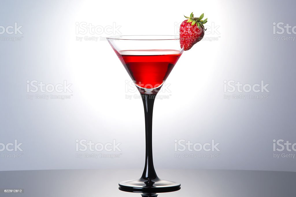 Red cocktail with liqueur and strawberry in martini glass stock photo
