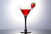 Red cocktail with liqueur and strawberry in martini glass