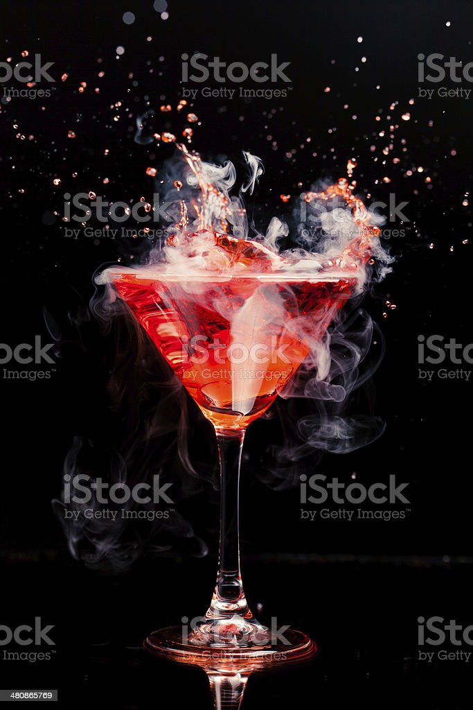 red cocktail with splash and ice vapor stock photo