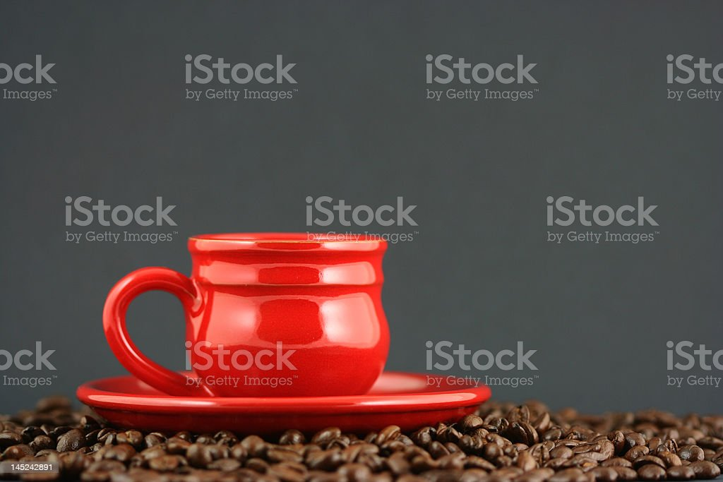 Red coffee cup and saucer on roasted beans stock photo