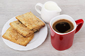 Red coffee cup, flaky cookies and milk jug on table