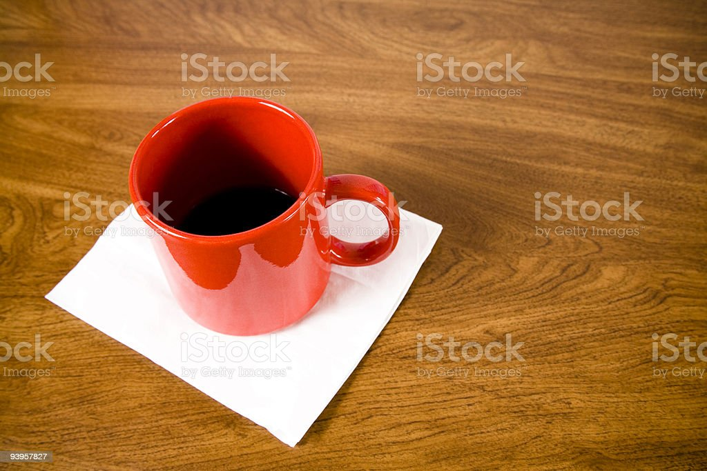 Red coffee mug with napkin on wood grained table royalty-free stock photo