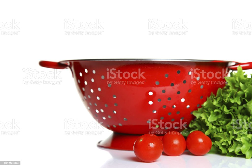 Red colander with lettuce and tomatoes stock photo