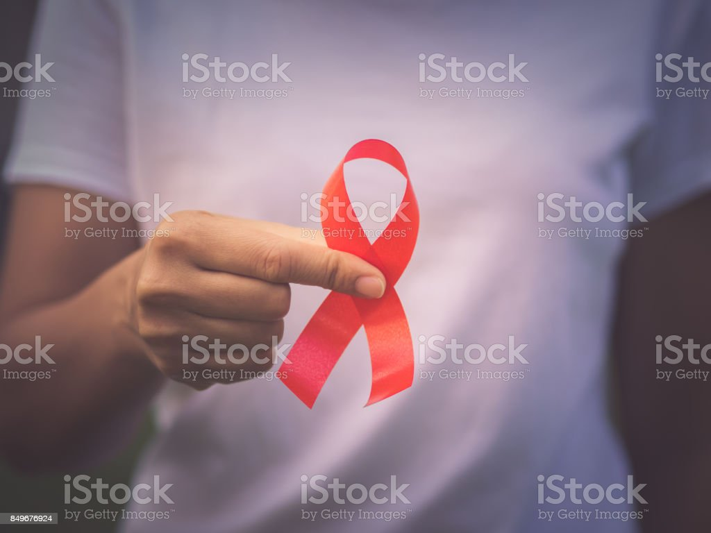 Red color ribbon awareness on young woman hand background: World aids day symbolic concept . stock photo