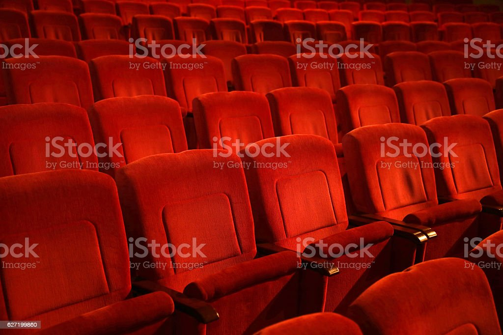 red colored empty movie theater chairs in row stock photo