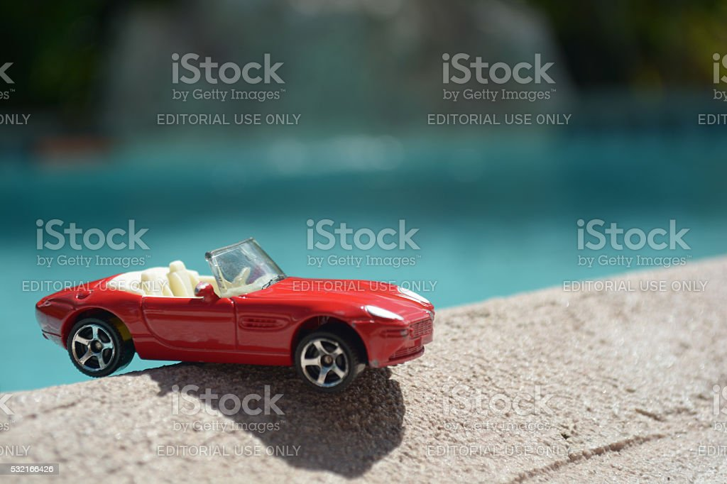 Red convertible toy car on the edge stock photo