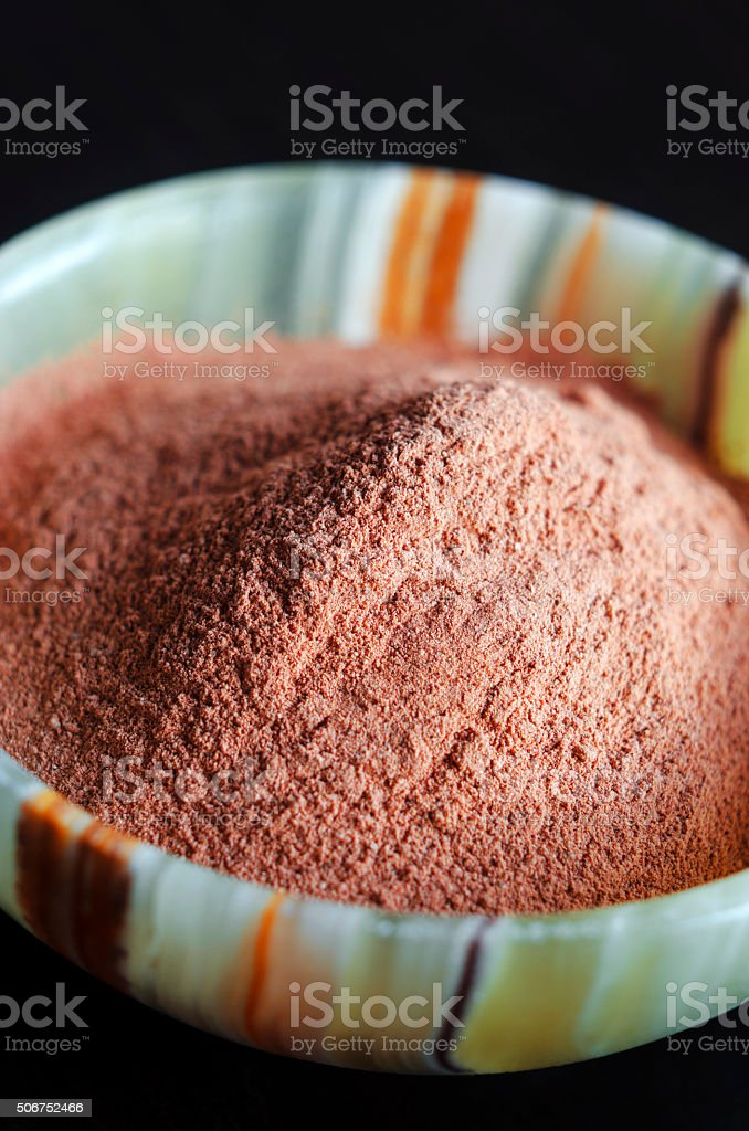 Red cosmetic clay powder in onyx bowl stock photo