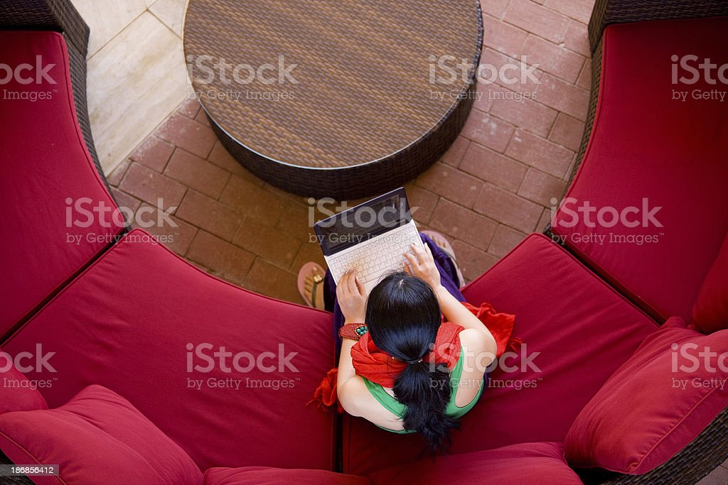 Red couch encircling table seats young woman with laptop royalty-free stock photo