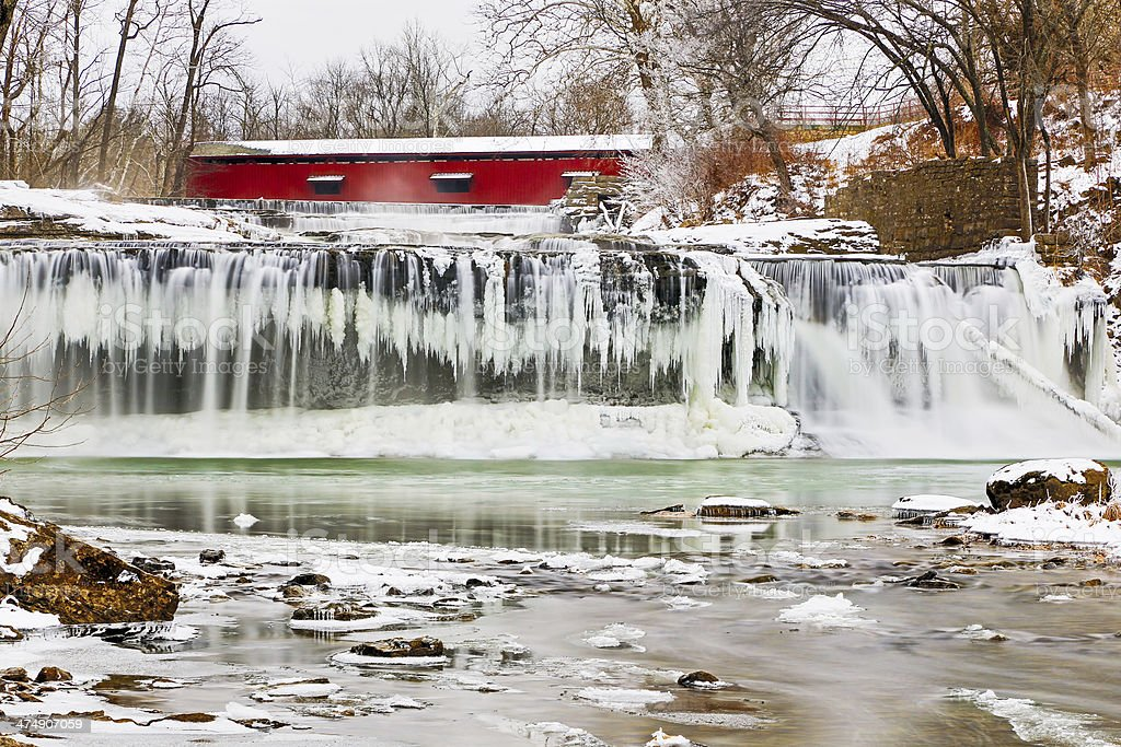 Red Covered Bridge and Frozen Waterfall stock photo