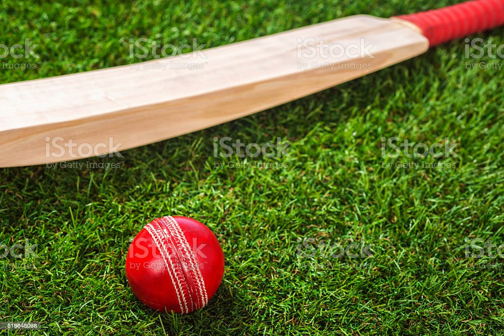 Red Cricket ball and bat sitting in grass sitting stock photo