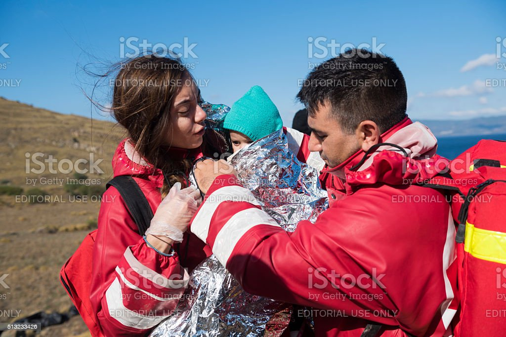 Red Cross volunteers helping refugees on Lesbos stock photo