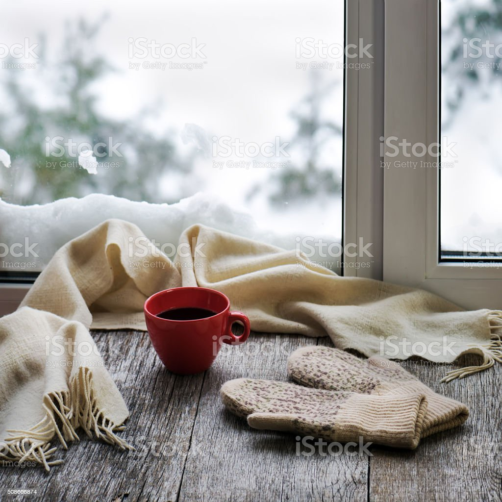 Red cup of coffee beige scarf and womans mittens. stock photo