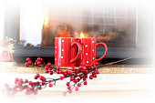 Red cup over fireplace on wooden table. Winter and Christmas
