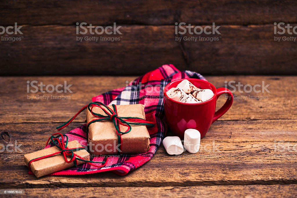 red cup with cocoa and marshmallows on wooden background stock photo
