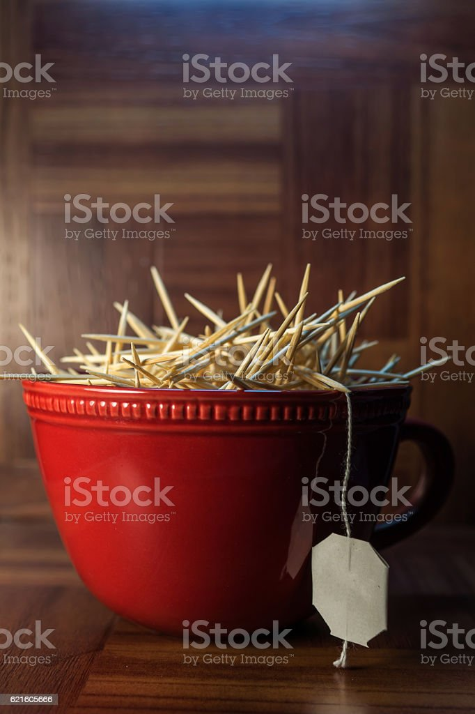 red cup with white tea tag, toothpicks, on wood stock photo