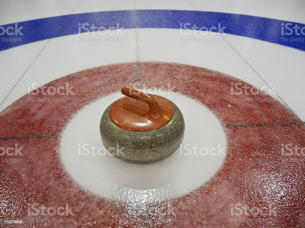 Red curling Rock in the center ice stock photo