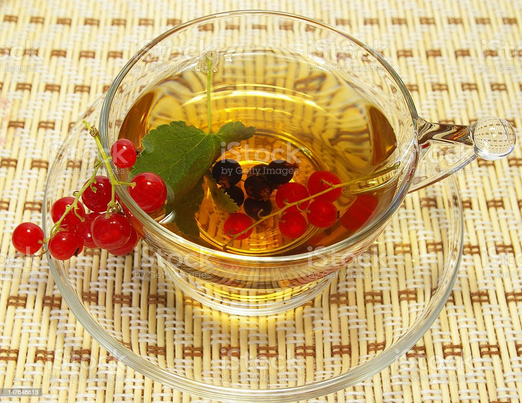 Red currant and tea in a transparent cup royalty-free stock photo