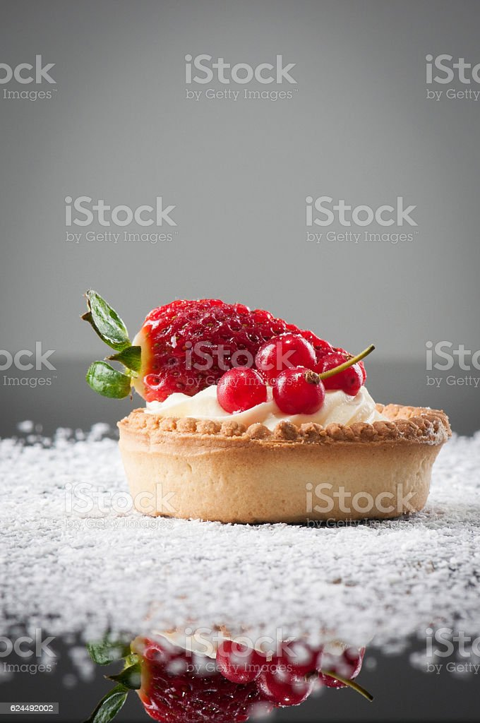 Red currants with strawberry and vanilla cream on a cookie stock photo