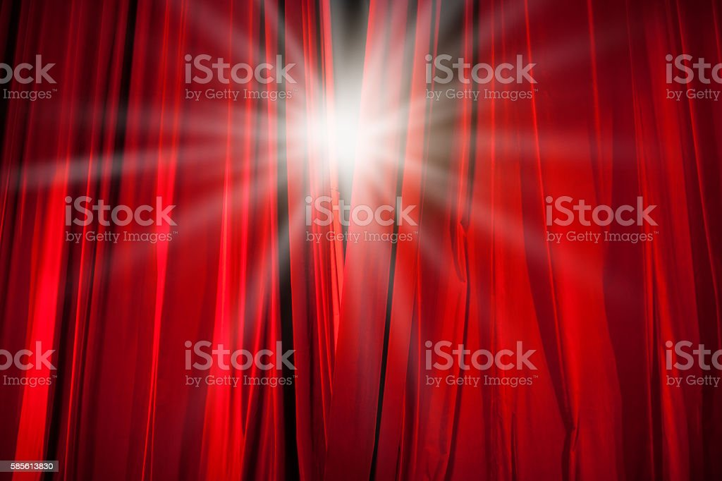 Red Curtain Opening with Stage Light Shining Through stock photo