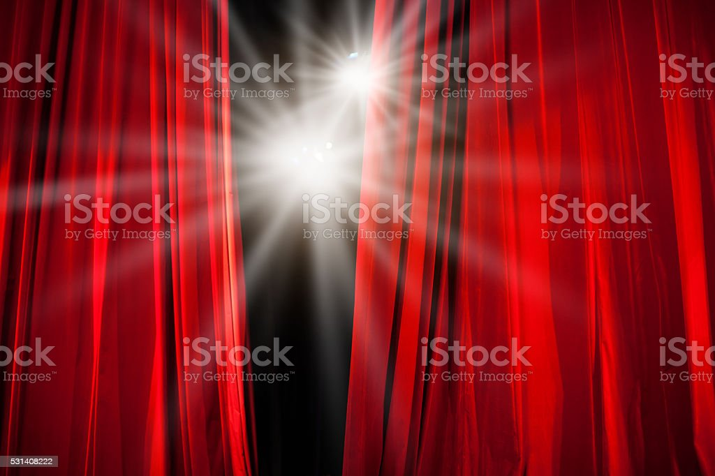 Red Curtain Opening with Stage Lights Shining Through stock photo