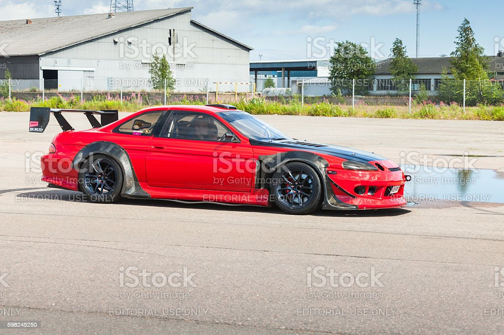 Red custom Toyota car goes down the street stock photo