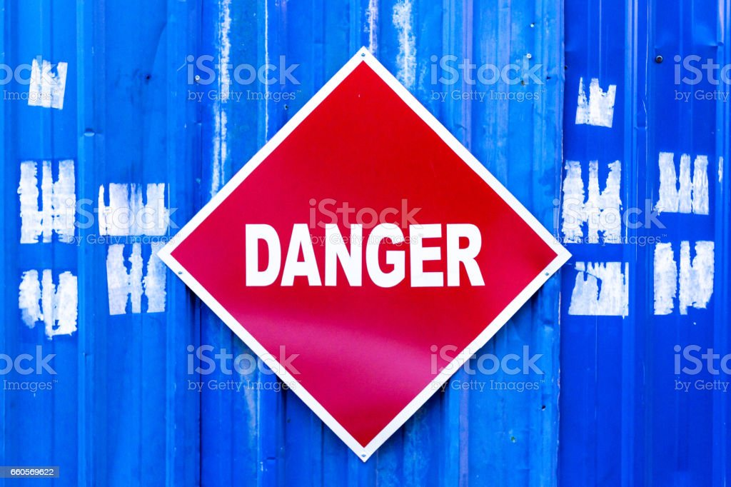 A red Danger sign mounted to a blue metal construction site wall. stock photo
