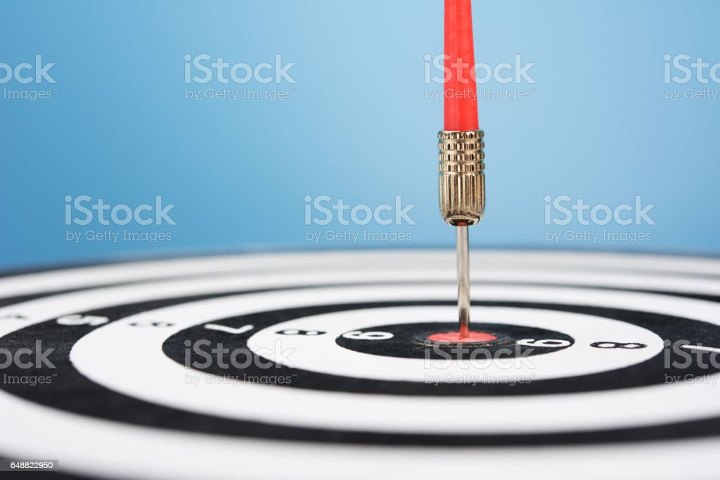 Red dart arrow hit target point center and blue background stock photo