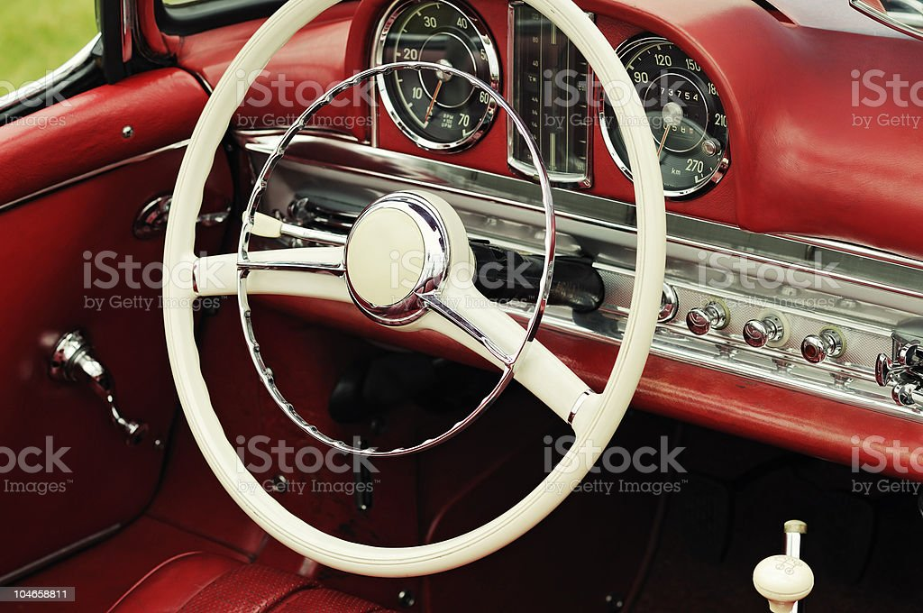 Red dashboard and white steering wheel of a vintage car royalty-free stock photo