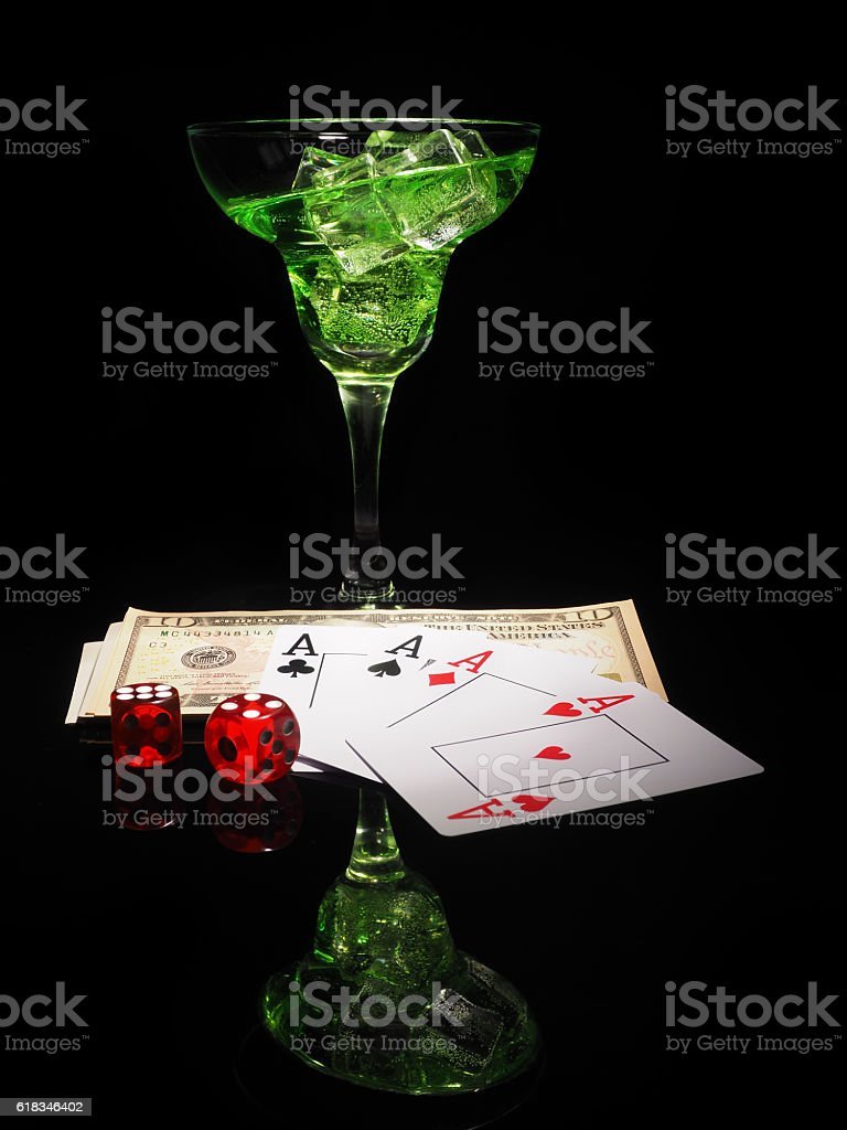 Red dice and a cocktail glass on black background. stock photo
