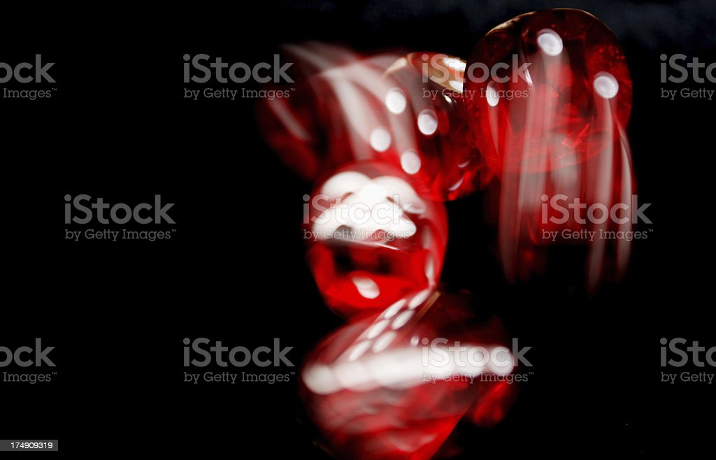 Red Dice being thrown with motion blur on black background royalty-free stock photo