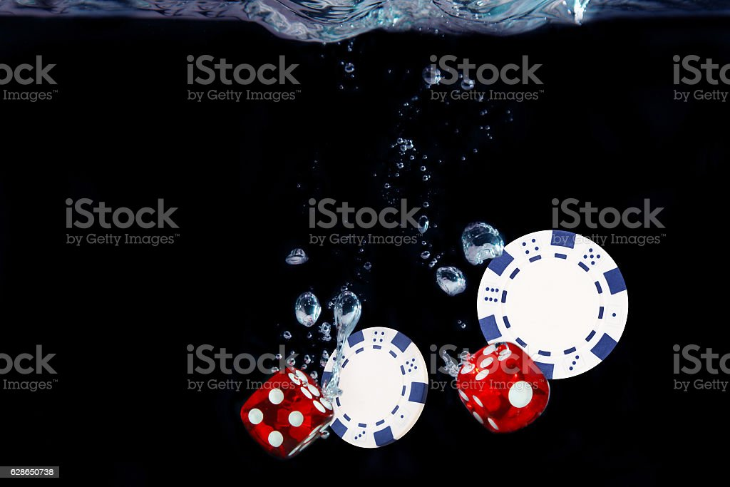 Red dice fall into the water. Casino concept stock photo