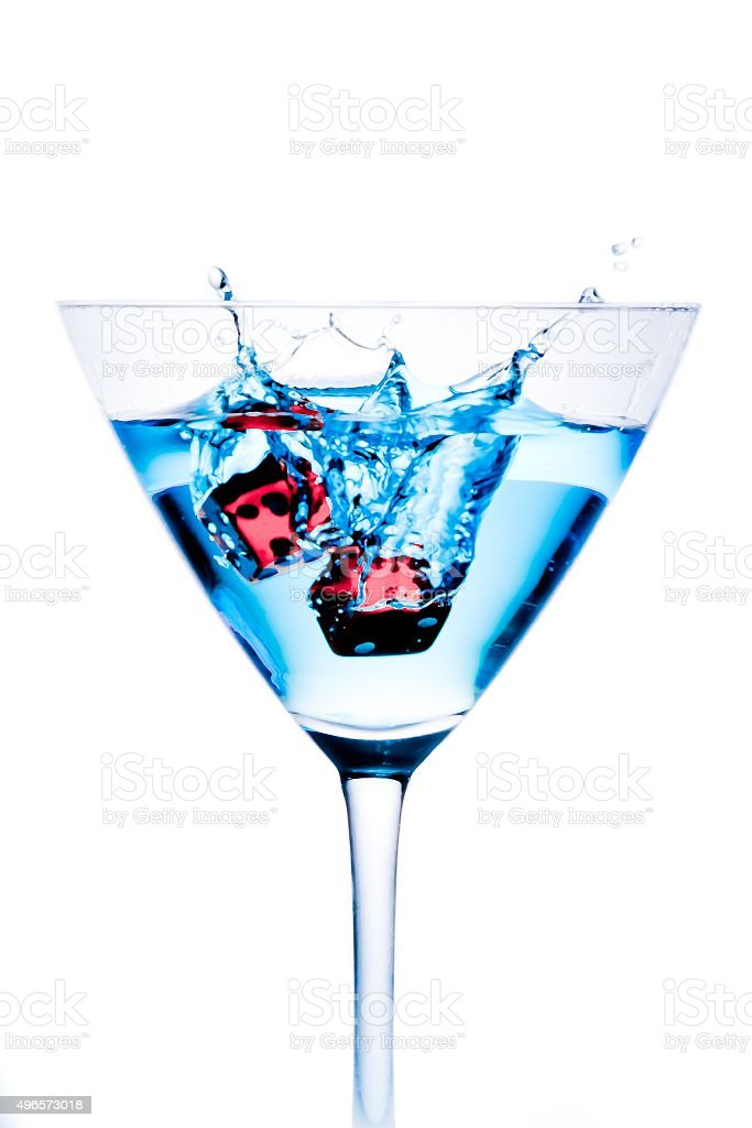 red dice falling in the blue cocktail glass with splashes stock photo