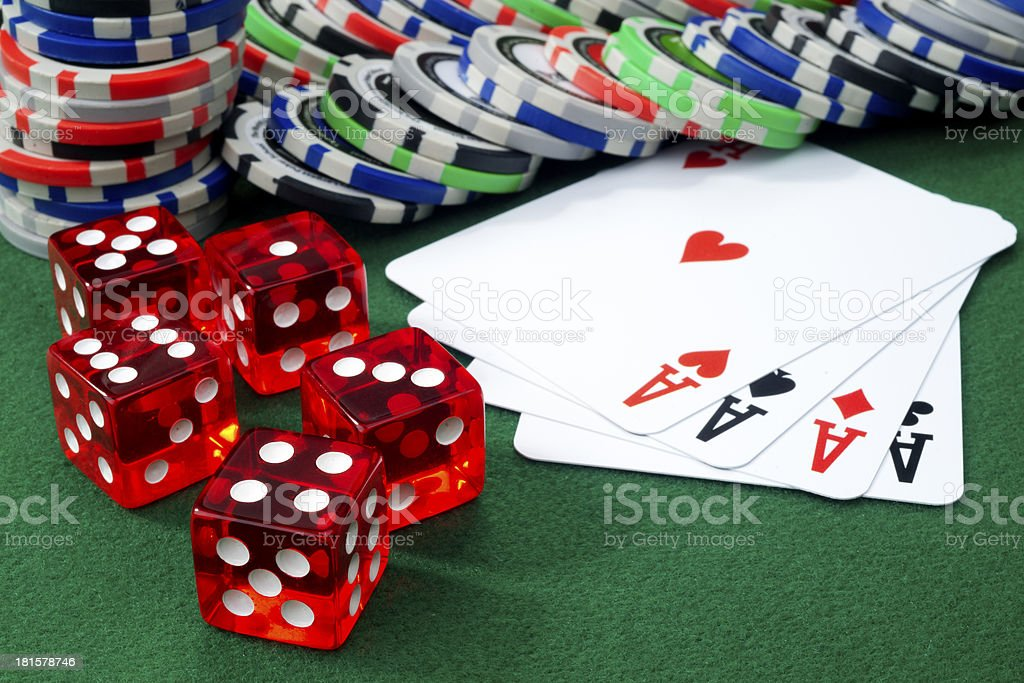 Red dice, four aces and chips on a green felt. royalty-free stock photo