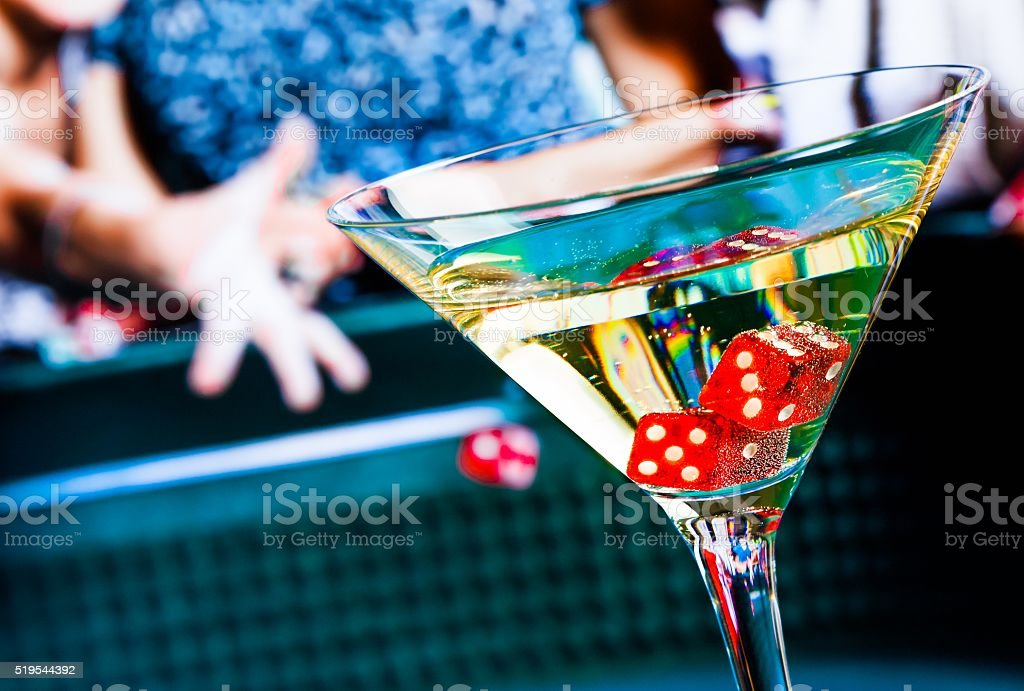 red dice in the cocktail glass in front of gambling stock photo
