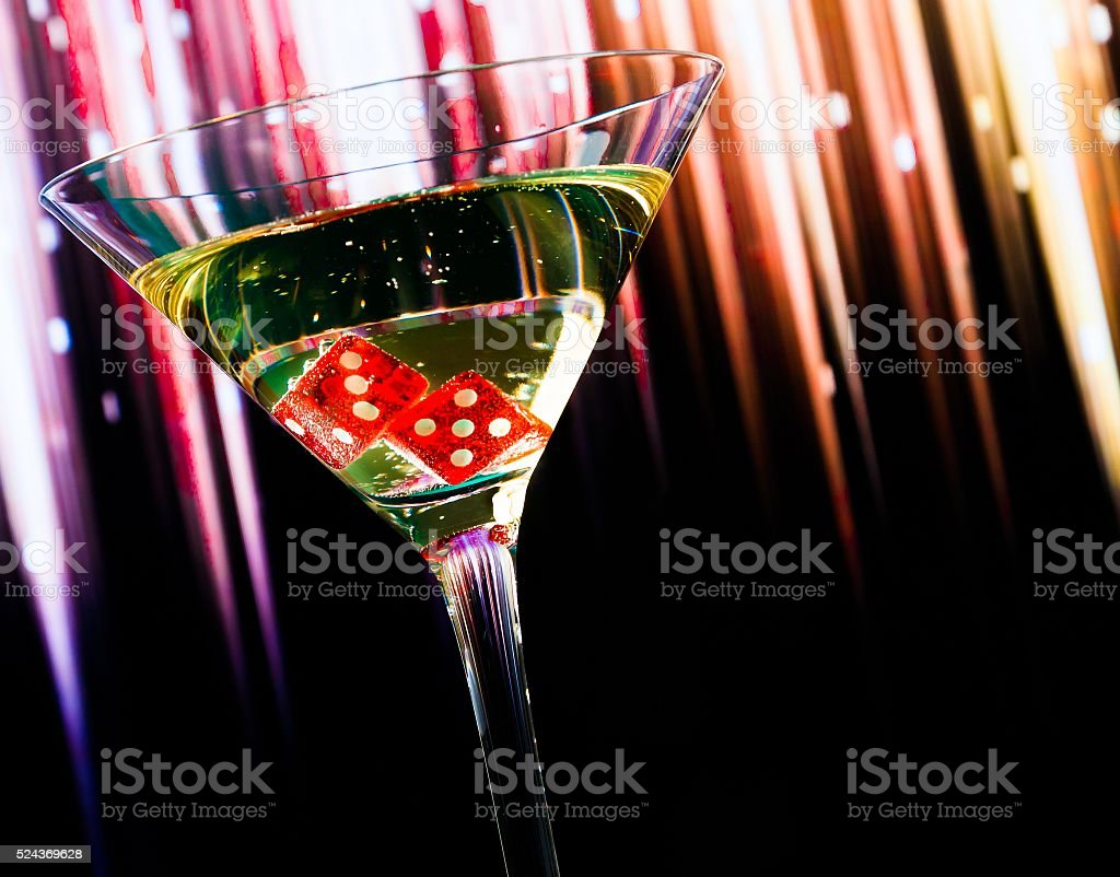 red dice in the cocktail glass on colorful gradient stock photo