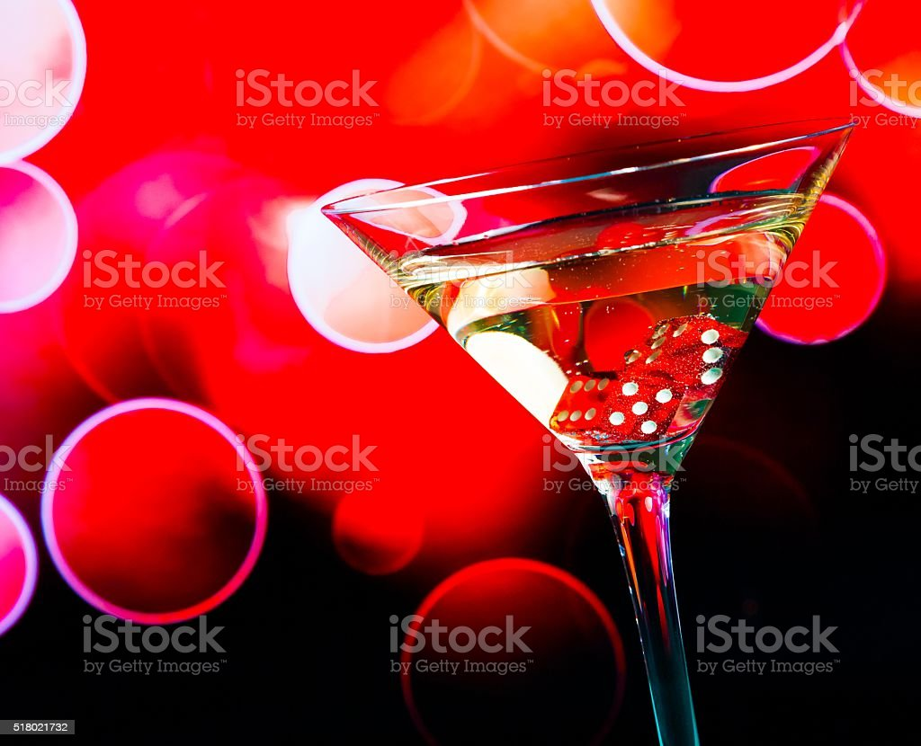 red dice in the cocktail glass on red bokeh stock photo
