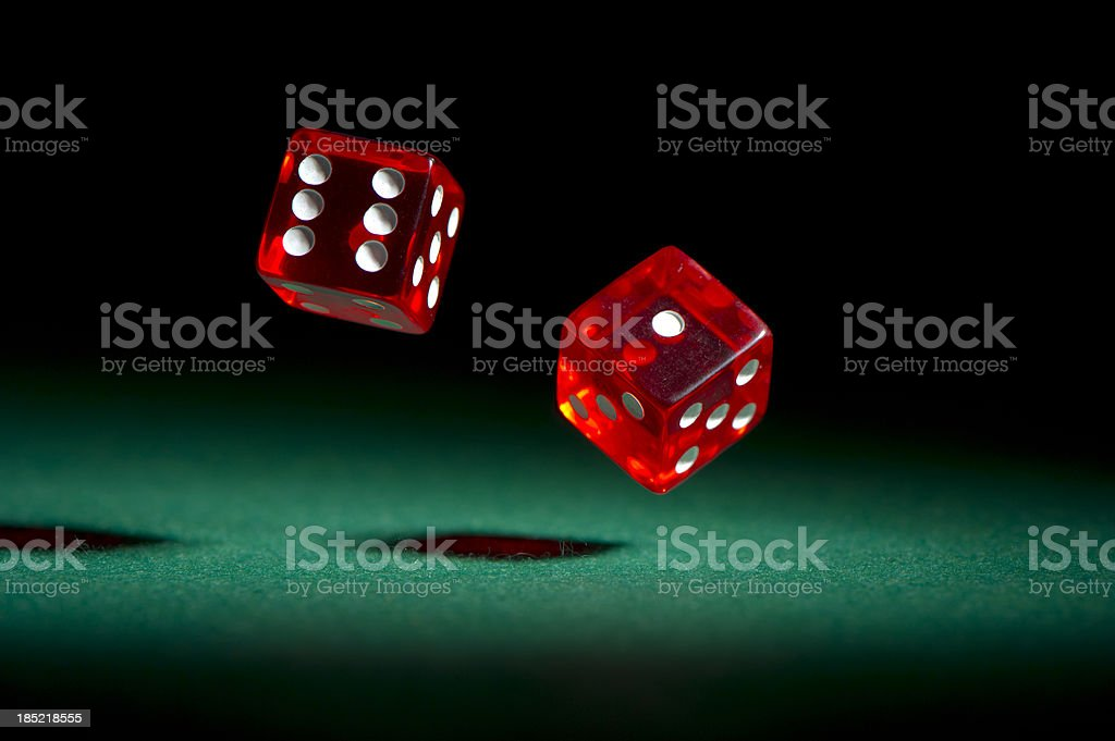Red dice rolling on green felt. stock photo