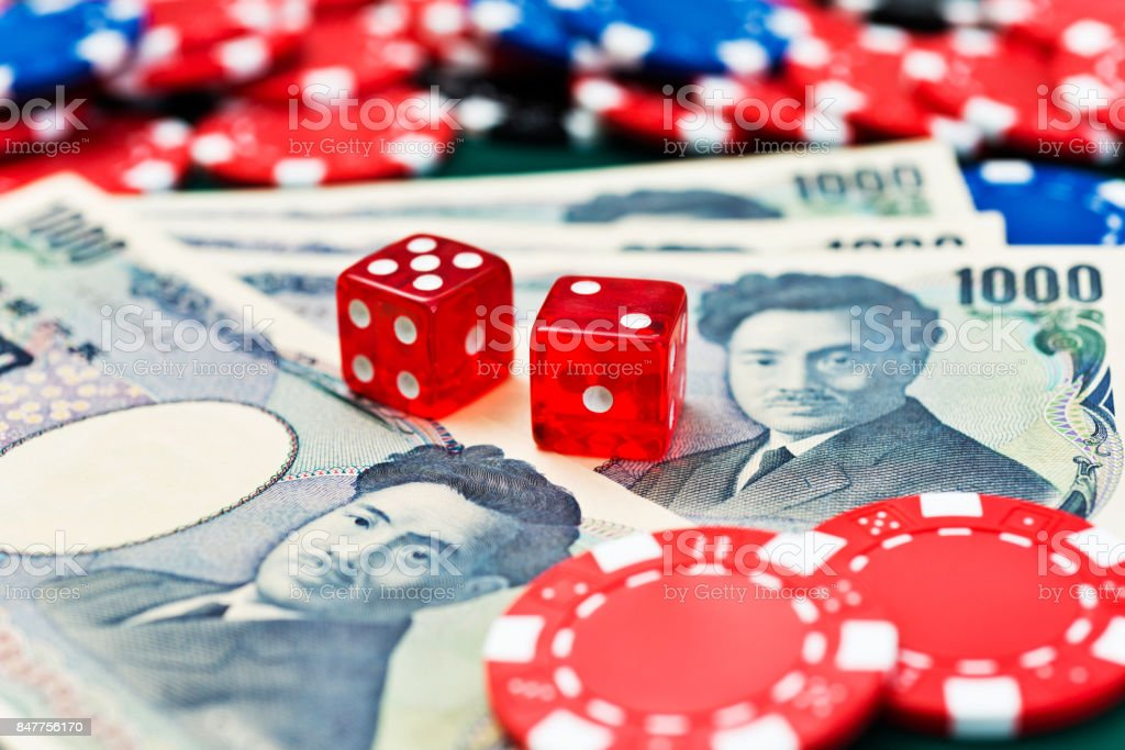 Red dices and japanese currency on the table stock photo