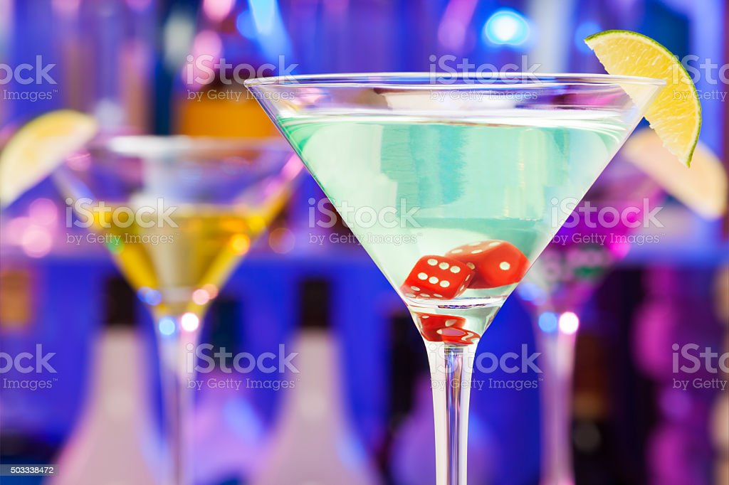 Red dices in cocktail glasses with bar on back stock photo