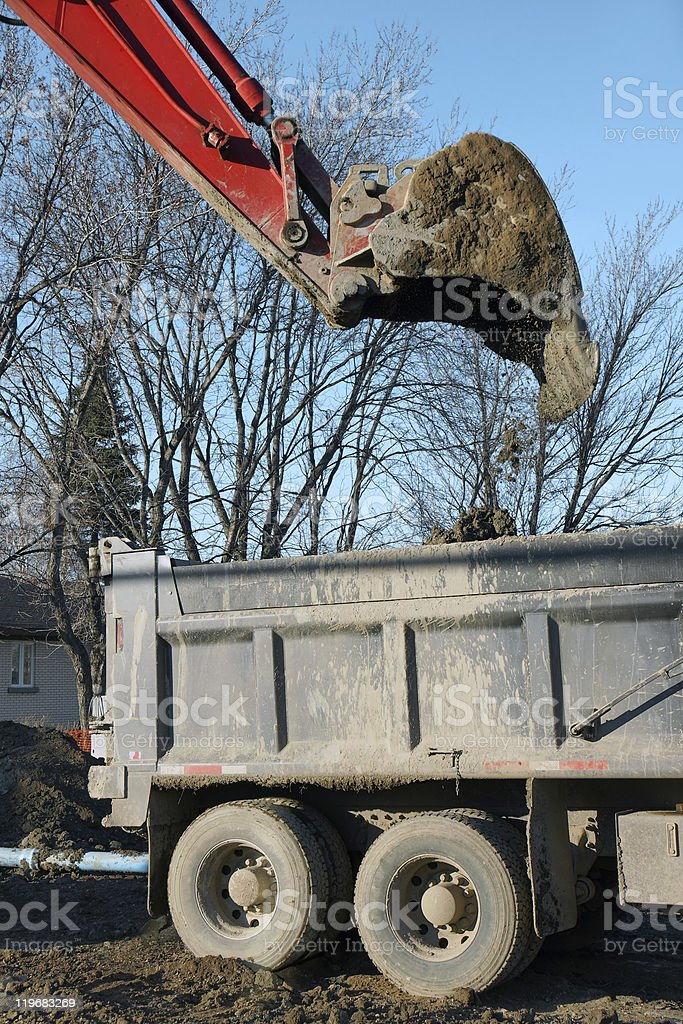 Red digger dumping dirt vertical stock photo