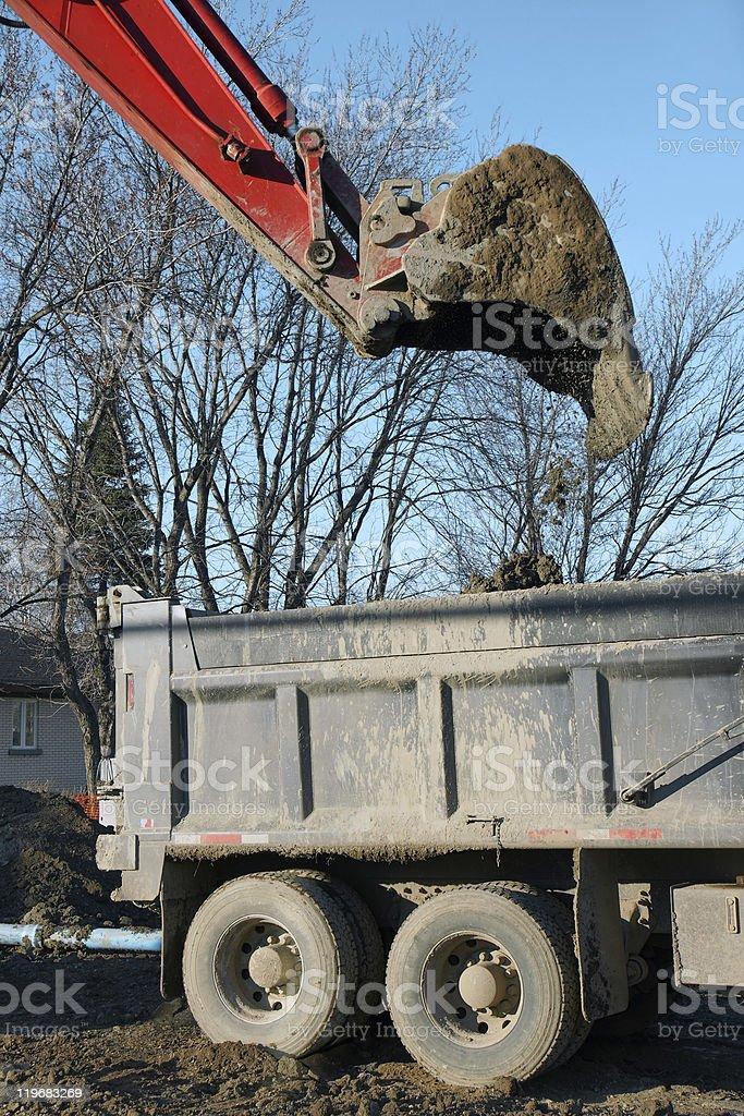 Red digger dumping dirt vertical stock photo