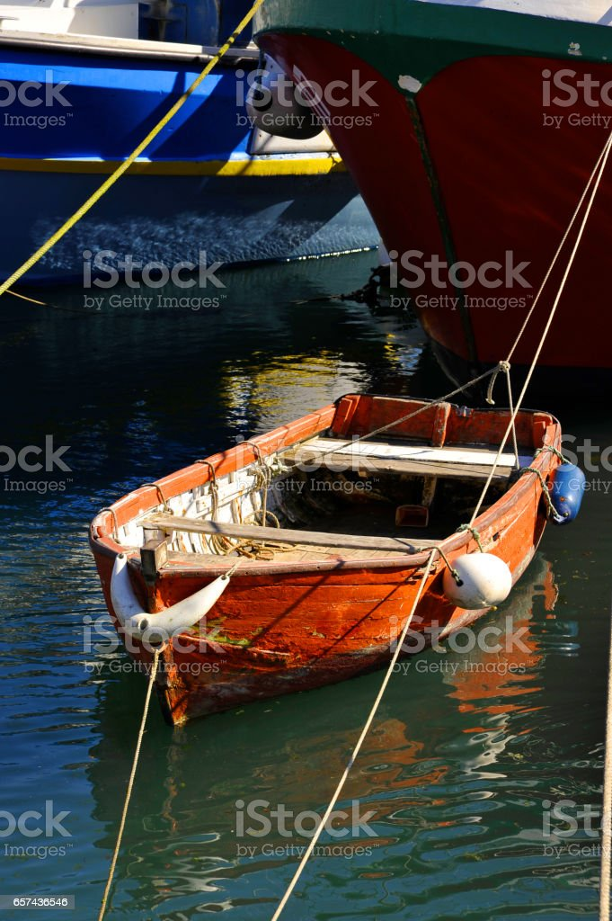 Red dinghy moored in harbour under bows of two other boats; sunny. stock photo