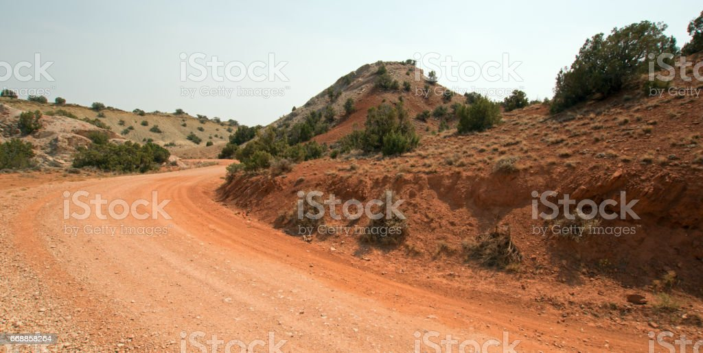Red dirt and gravel Crooked Creek Road through the Pryor Mountains in Montana USA stock photo